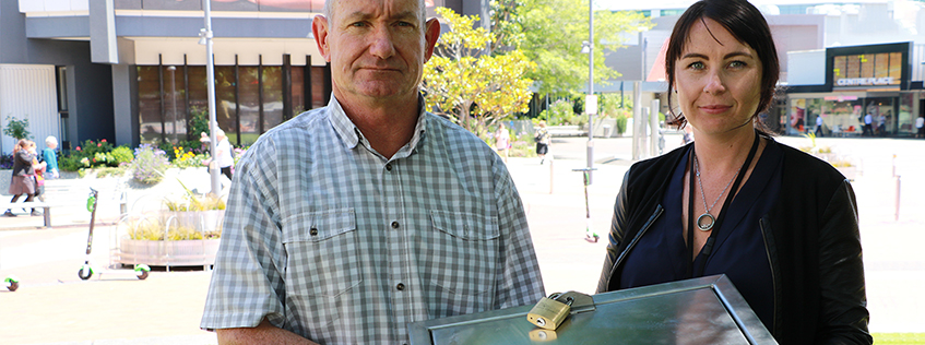 Ross Brunton and Jade Murray with the heavy duty toilet roll holder Hamilton City Council has been forced to use in public toilets that are frequently vandalised.