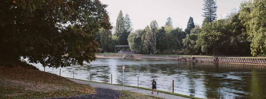 Image of man running along Waikato River