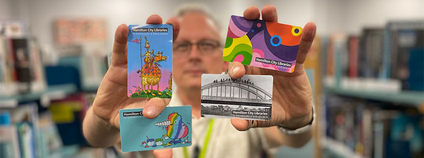 Hamilton City Libraries Director Stephen Pennruscoe with the four new library card designs.